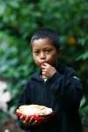 Ecuadorianischer Junge mit Kakaofrucht